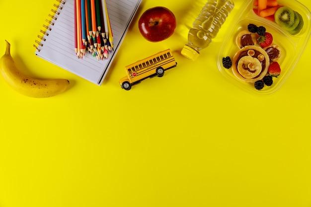 Terug naar school-concept. lunchbox met pannenkoeken, wortel, appel en banaan met scoolbenodigdheden.