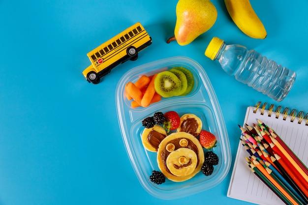 Terug naar school-concept. lunchbox met pannenkoeken, wortel, peer en banaan met scoolbenodigdheden.