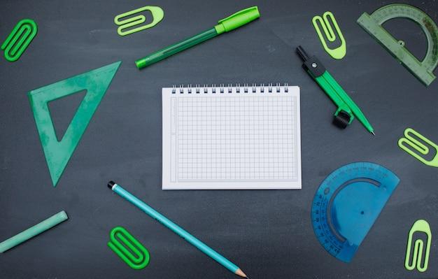 Terug naar school concept met notebook, pen, potlood, krijt, kompas, paperclips, linialen op grijze achtergrond plat lag.