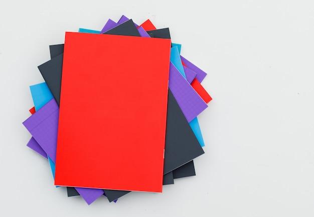 Terug naar school concept met veelkleurige notebooks op witte muur plat lag.