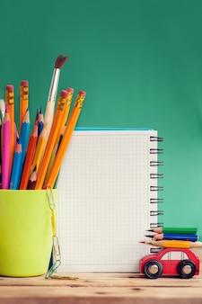 Terug naar school-concept. miniatuur rode auto met een kleurrijke potloden en rode appel op houten tafel