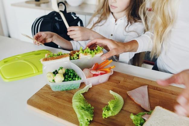 Terug naar school-concept moeder bereidt broodjes voor kinderen voor op school
