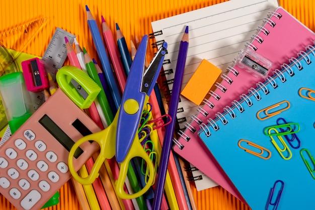 Terug naar school concept. notebook en onderwijs apparatuur op oranje achtergrond.