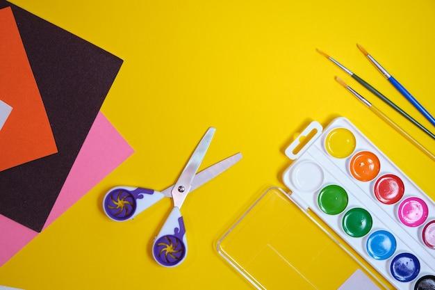 Terug naar school-concept, penseel, aquarelverf, schaar en gekleurd papier op gele achtergrond, kopie ruimte, bovenaanzicht