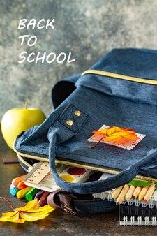 Terug naar school concept schoolbenodigdheden met blauwe rugzak op tafel