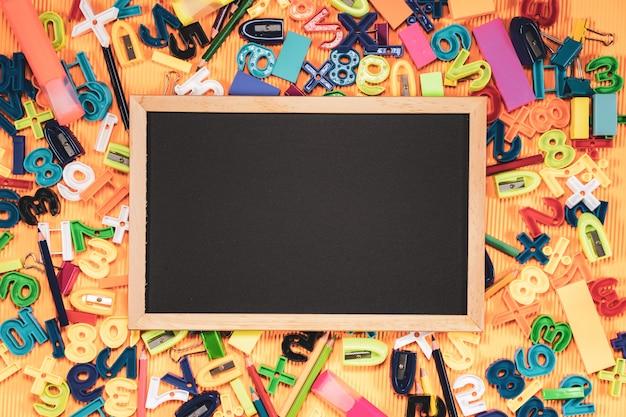 Terug naar school concept. schoolbord en onderwijsmateriaal op oranje achtergrond.