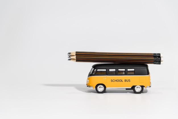 Terug naar school concept. schoolbus dragen potloden op wit