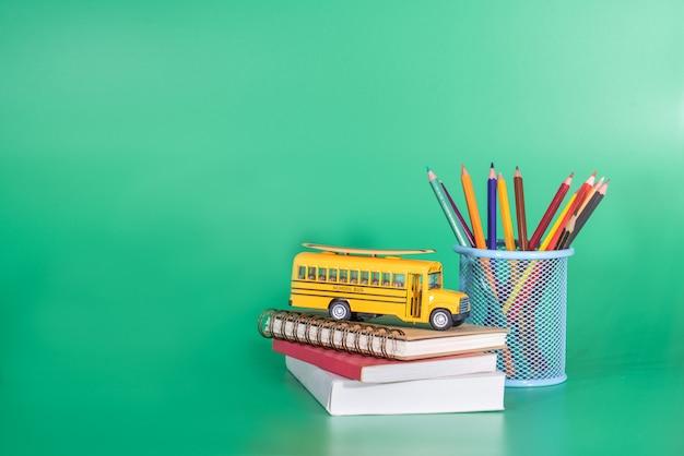 Terug naar school concept. schoolbus op het boek met schoolbenodigdheden