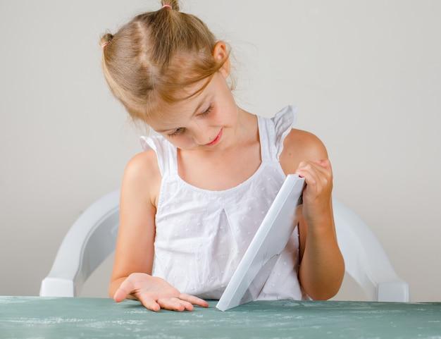 Terug naar school concept zijaanzicht. klein meisje kijken naar boekomslag.
