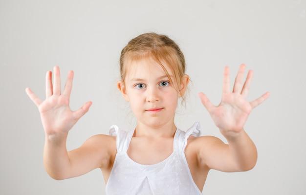 Terug naar school concept zijaanzicht. klein meisje toont haar handpalmen.