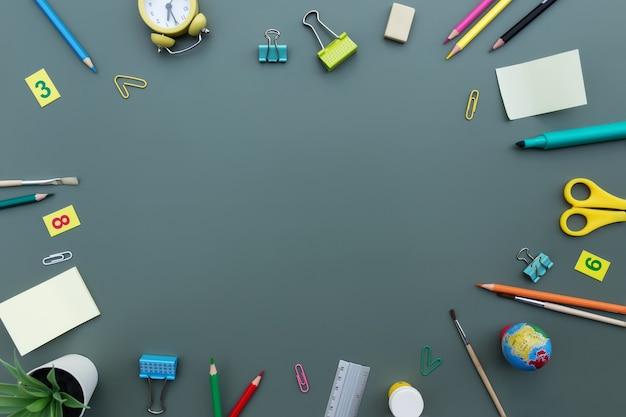 Terug naar school conceptuele flat lag met verschillende kantoorbenodigdheden en kopieerruimte voor tekst. concept voor basisschoolleerling op groene achtergrond. wekker, gum, liniaal