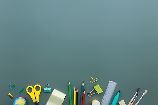Terug naar school conceptuele flat lag met verschillende kantoorbenodigdheden op groene achtergrond. concept voor basisschoolleerlingen en middelbare scholieren. schaar, pen, potlood, gum, liniaal, notitie, clip