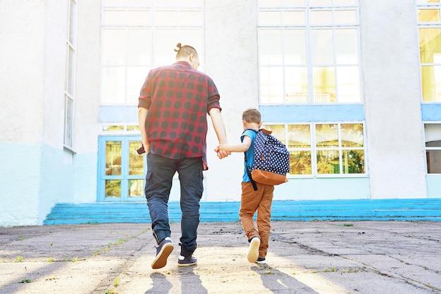 Terug naar school. de gelukkige vader en de zoon gaan naar basisschool