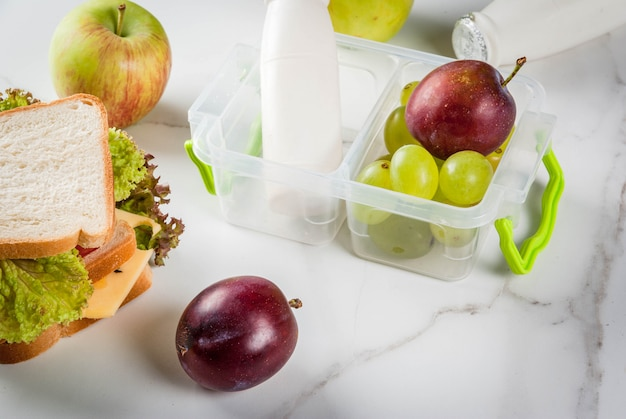 Terug naar school. een gezonde lunch in een doos is verse fruitappels, pruimen, druiven, een fles yoghurt en een broodje met sla, tomaten, kaas, vlees. witte marmeren tafel.