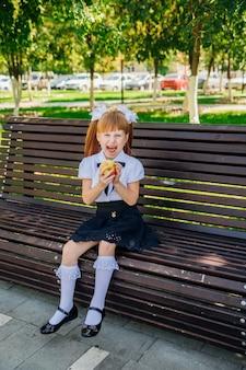 Terug naar school. een schattig klein schoolmeisje zit op een bankje op het schoolplein en bijt een groene appel. goede schoolmaaltijden voor de lunch. een klein meisje gaat naar het eerste leerjaar. kennisdag.