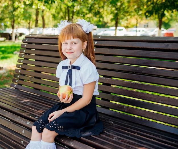 Terug naar school. een schattig klein schoolmeisje zit op een bankje op het schoolplein en houdt een groene appel vast.