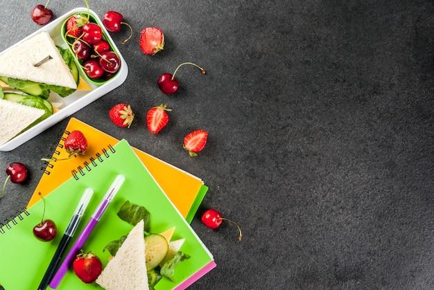 Terug naar school. een stevige gezonde schoollunch in een doos: broodjes met groenten en kaas, bessen en fruitappels met notitieboekjes, gekleurde pennen op een zwarte tafel.