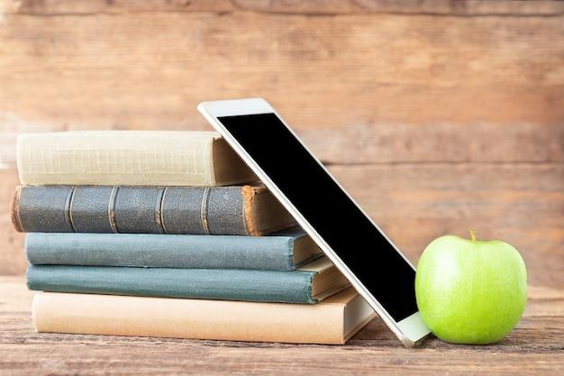 Terug naar school en onderwijsconcept een stapel boekentabler en groene appel op een houten achtergrond