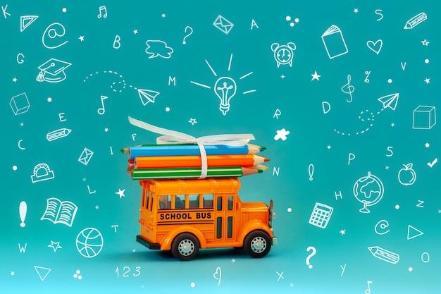 Terug naar school en onderwijsconcept. gele retro schoolbus draagt potloden op dak op blauwe achtergrond met schoolkantoorbehoeften.