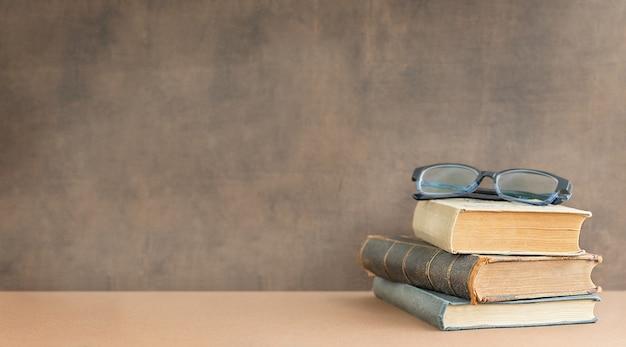 Terug naar school en onderwijsconcept stapel boeken en glazen op de bovenkant dichtbij het bord en plaats voor tekst