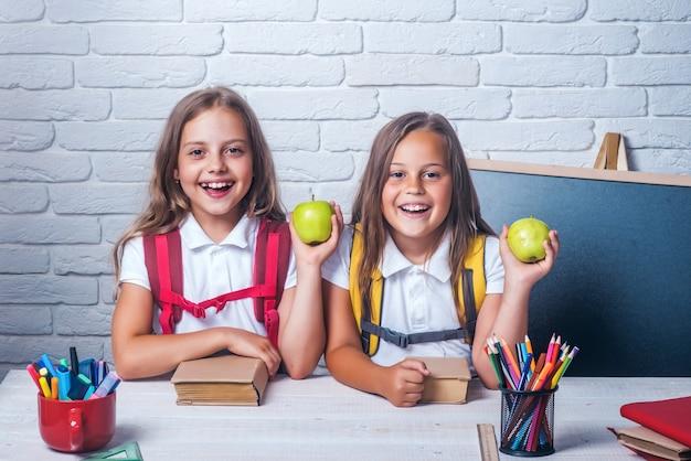 Terug naar school en thuisonderwijs. vriendschap van kleine zusjes in de klas op kennisdag. kleine meisjes eten appel tijdens de lunchpauze. schooltijd van meisjes. gelukkige schoolkinderen bij les.