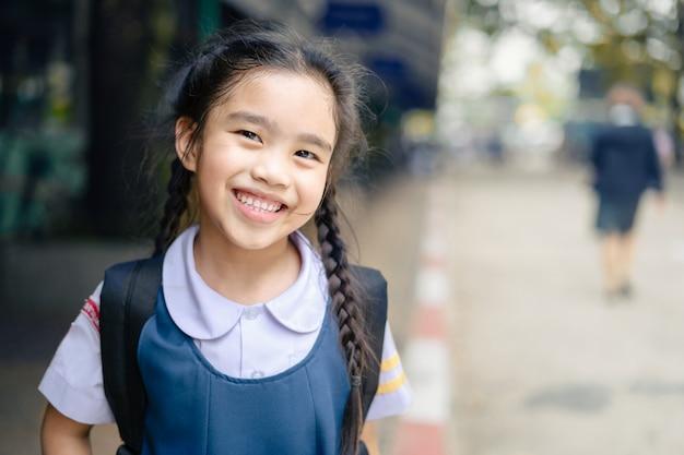 Terug naar school. gelukkig lachend meisje van basisschool op het schoolplein