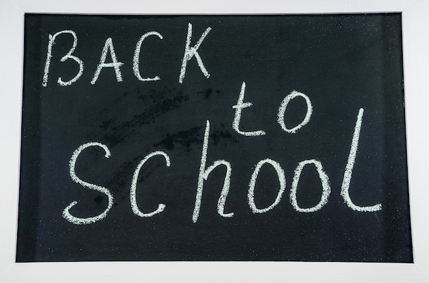 Terug naar school geschreven met krijt op een zwart schoolbord