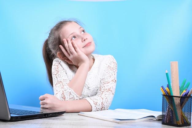 Terug naar school. het gelukkige leuke ijverige kind zit binnen bij een bureau. kind leert in de klas met laptop, computer