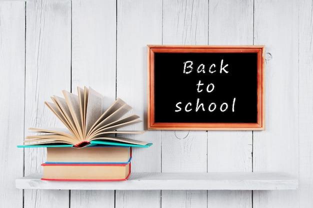 Terug naar school. het open boek over andere veelkleurige boeken. op een houten plank.