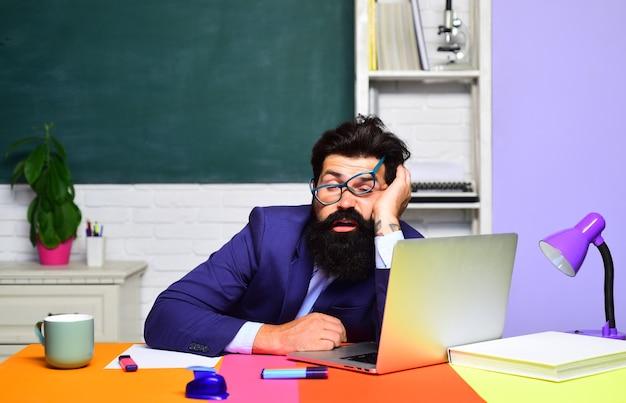 Terug naar school kennis en educatief schoolconcept moe leraar slapen in de klas hard