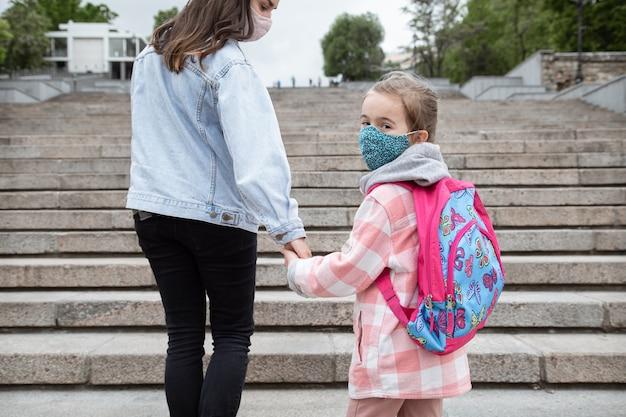Terug naar school. kinderen met een coronavirus-pandemie gaan met maskers naar school. vriendschappelijke betrekkingen met mijn moeder.