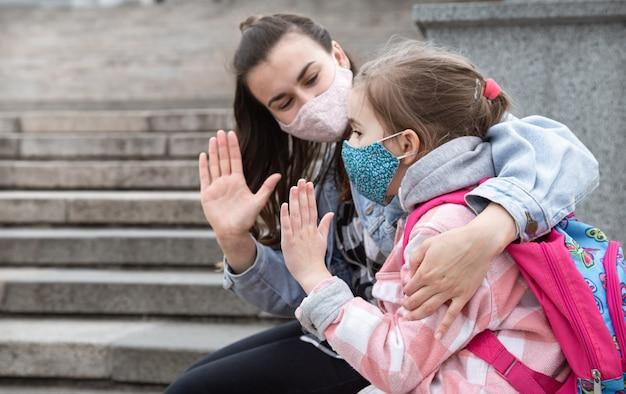 Terug naar school. kinderen met een coronavirus-pandemie gaan met maskers naar school. vriendschappelijke betrekkingen met moeder. kinderopvoeding.