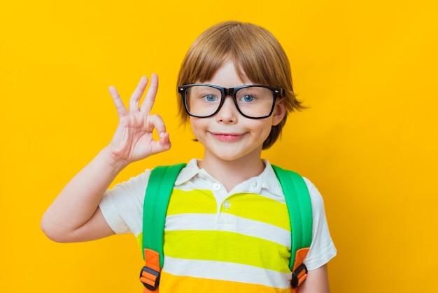 Terug naar school. kleine jongen in bril met tas toont ok of ok-teken