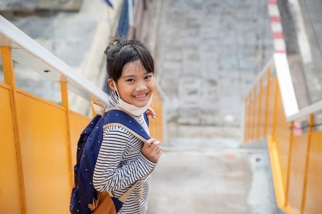Terug naar school. leuk aziatisch kindmeisje met rugzak en naar school gaand