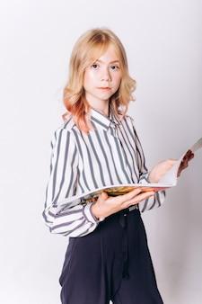Terug naar school. leuk schattig kaukasisch blondie meisje met boek in schooluniform op witte achtergrond