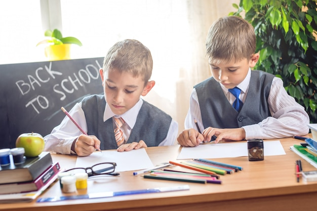 Terug naar school. leuke kinderen die bij het bureau in het klaslokaal zitten.