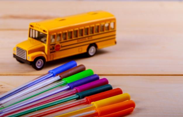 Terug naar school levert kleurpotloden speelgoed gele schoolbus op houten achtergrond