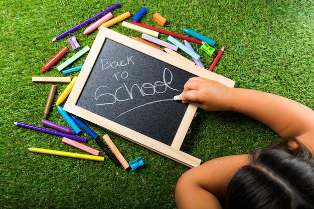 Terug naar school levert regeling levendige kleurrijke op groen gras en schoolbord hand krijt