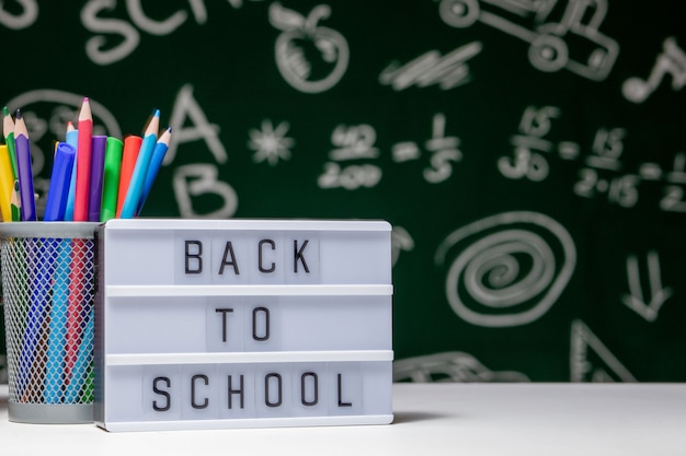 Terug naar school met boeken, potloden en globe op witte tafel op groene schoolbord