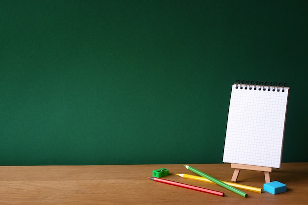 Terug naar school met open notitieboekje op miniatuur-ezel en verschillende kleurpotloden op houten oppervlak op de achtergrond van een schoon groen schoolbord