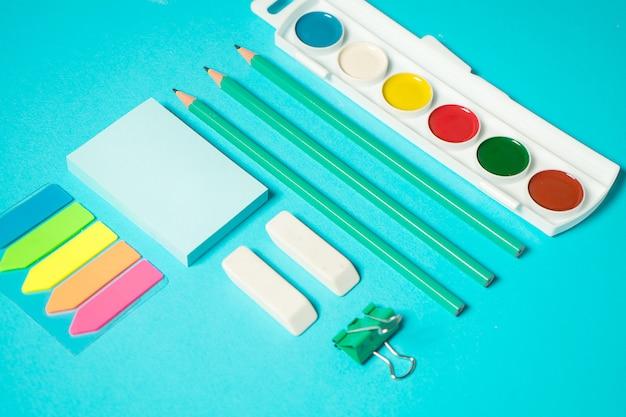 Terug naar school mock up. plat lag samenstelling met een aquarel, potlood, sticker, gum. isometrisch concept op blauwe achtergrond. pop art. schoolspullen. overhead. branding mock up briefpapier