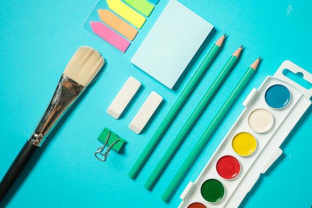 Terug naar school mock up. plat lag samenstelling met een penseel, aquarel, potlood, sticker, gum. isometrisch concept op blauwe achtergrond. pop art. schoolspullen. overhead. branding mock up briefpapier