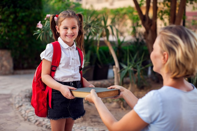 Terug naar school. moeder geeft een boek aan haar kind voordat ze naar school gaat
