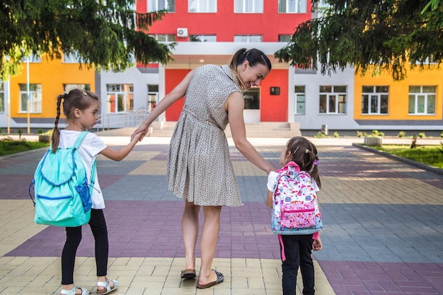 Terug naar school onderwijsconcept met meisjeskinderen, elementaire studenten, die rugzakken dragen die naar klasse gaan