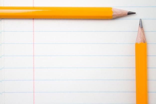 Terug naar school, onderwijsconcept met oranje potloden dichte omhooggaand en samenstellingsboek