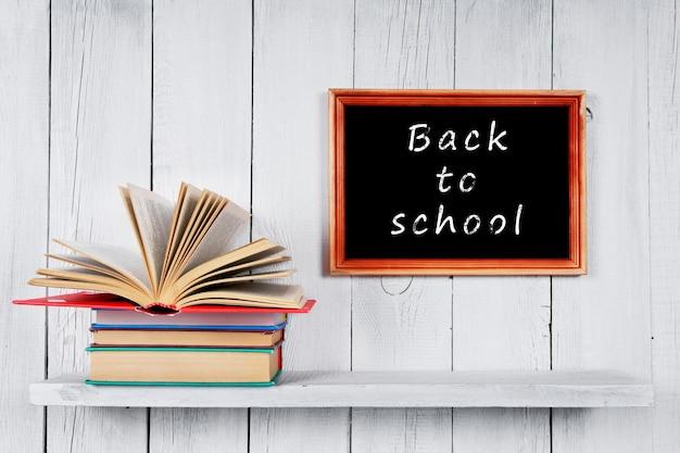 Terug naar school. open boek over andere veelkleurige boeken op houten plank.