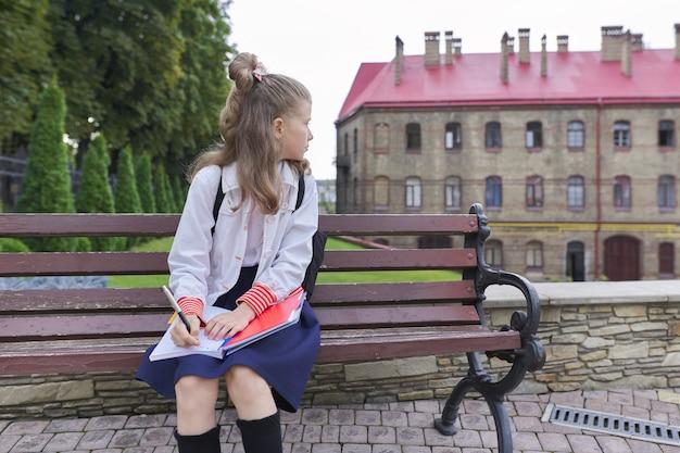Terug naar school. openluchtportret van mooi blond meisje dat met rugzak in notitieboekje schrijft