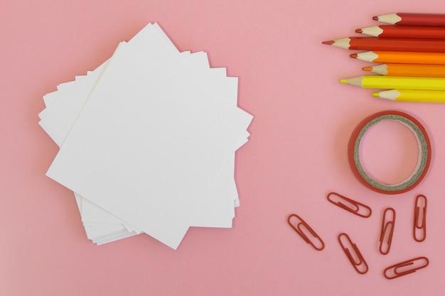 Terug naar school . papier voor het schrijven met potloden, clips en plakband op een roze achtergrond.