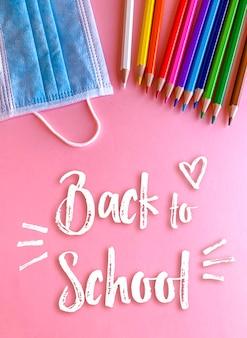 Terug naar school, potloden en masker op roze achtergrond