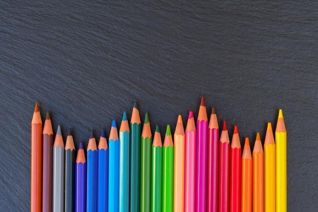 Terug naar school potloden kleur regenboog rand op zwarte bord achtergrond met kopie ruimte, bovenaanzicht